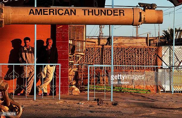 Iraqi men in the sprawling Iraqi Shia slum of Sadr City are seen framed by the barrel of an American tank following clashes in the sprawling Iraqi...