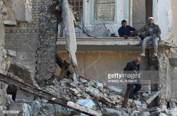 Iraqi men inspect a house which was destroyed during the battles in the old city of Mosul on January 9 2018 Along the waterfront of the Tigris River...