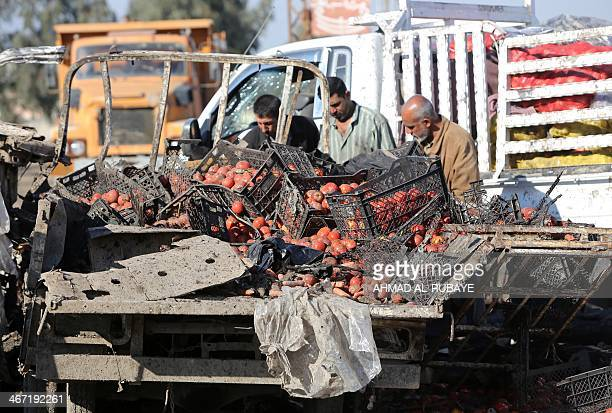 Iraqi men inspect damaged tomatoes at the site of car bomb explosions on February 6 2014 in alObeidi Shiite neighbourhood on the eastern outskirts of...