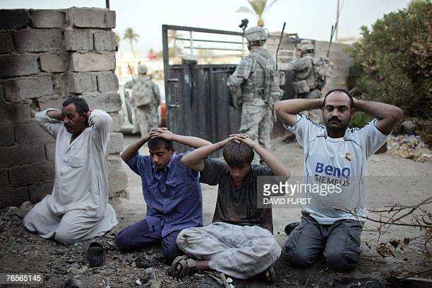Iraqi men kneel with their hands up as they are temporarily detained by US soldiers from 140 Cavalry Squadron in the Hawra Haajab village on the...