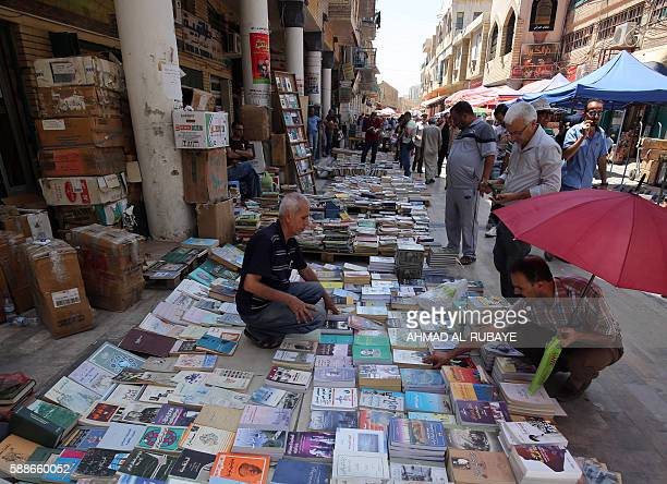 Iraqi men look at books displayed by a street vendor on alMutanabbi street in central Baghdad on August 12 2016 / AFP / AHMAD ALRUBAYE
