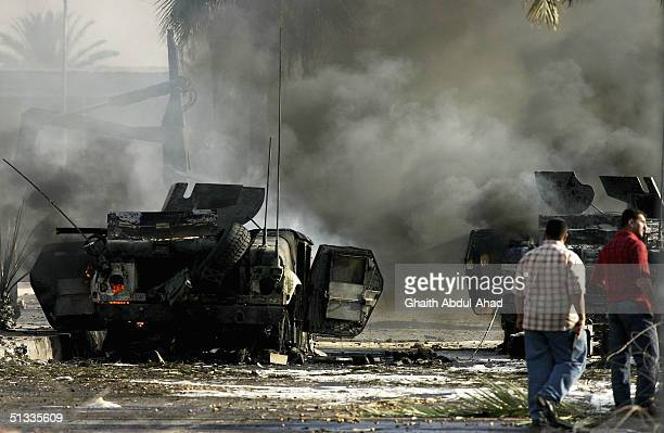 Iraqi men look at two wrecked humvees belonging to the 1st Marine Expeditionary Force are seen September 22 2004 in the Mansour district of Baghdad...