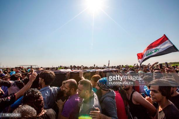 TOPSHOT Iraqi men march with a coffin draped with a national flag in a funerary procession for a protester who was killed earlier in the day outside...