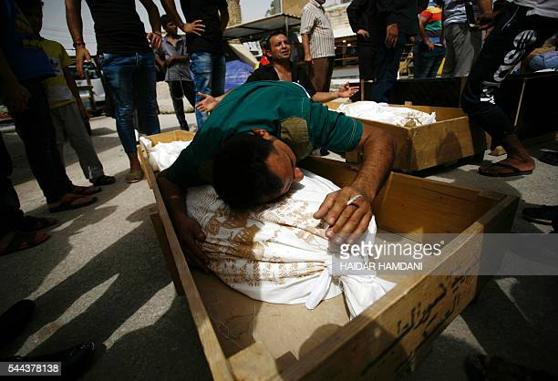 TOPSHOT Iraqi men mourn over bodies after they lost five members of their family in a suicide bombing that ripped through Baghdad's busy shopping...