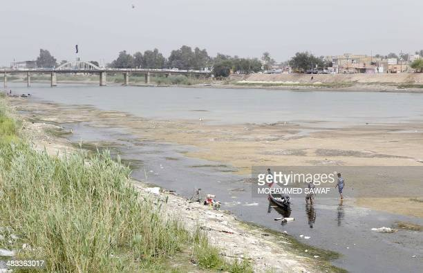 Iraqi men move a boat that was stuck on the banks of the Euphrates river in Twairij roughly 20 kilometres east of Karbala due to a decline in the...