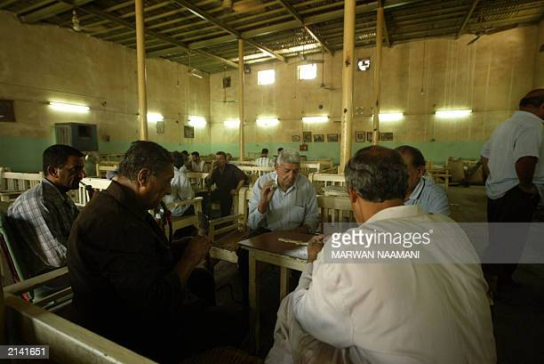 Iraqi men play a game of dominos at the AlMustansiriyah coffee shop in central Baghdad 22 June 2003 The coffee shop was built in 1587 and housed...