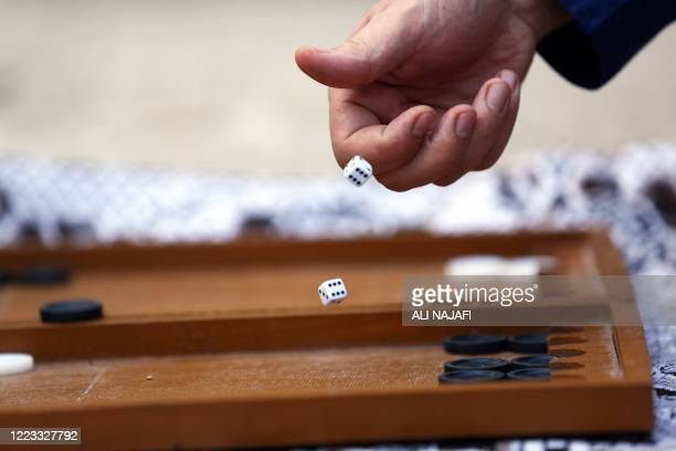 Iraqi men play backgammon on the roof of a building amid a total curfew due to the COVID-19 pandemic, in the central city of Najaf, on June 28, 2020.