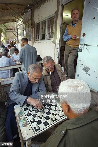 Iraqi men play chess at a cafe in the predominantly Sunni Muslim Azamiyah neighborhood of Baghdad 28 November 2003 Former US first lady Senator...
