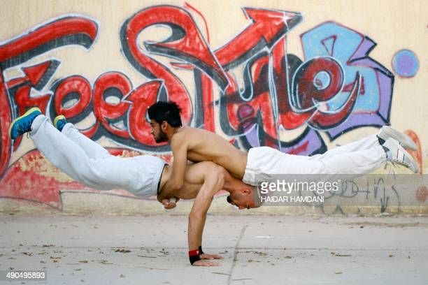 Iraqi men practice parkour, a fast-moving sport blending acrobatics and gymnastics, on May 14, 2014 in the central shrine city of Najaf. AFP PHOTO /...
