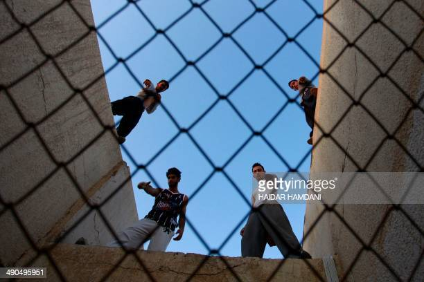 Iraqi men practice parkour a fastmoving sport blending acrobatics and gymnastics on May 14 2014 in the central shrine city of Najaf AFP PHOTO /...