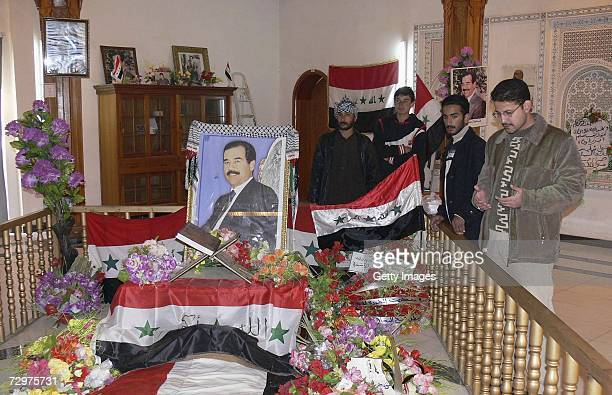 Iraqi men pray at the grave of Iraqs former President Saddam Hussein on January 11 2007 in his home town Awja in Tikirt province 80 miles north of...