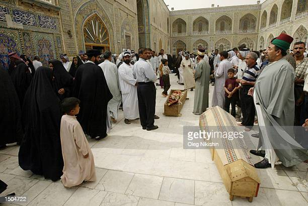 Iraqi men pray during a ceremony of the last word at a mosque named the Shrine of the Imam Ali Ibn Abi Talib October 18, 2002 in the town known as...