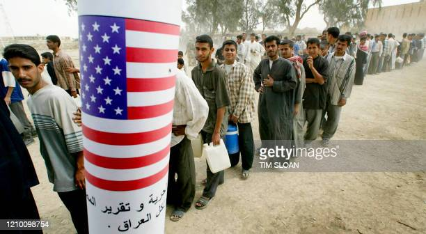 Iraqi men queue for food rations at the humanitarian aid site run by the US Marine's 15th MEU 10 April 2003 in the city of Nasiriyah in Iraq. As the...