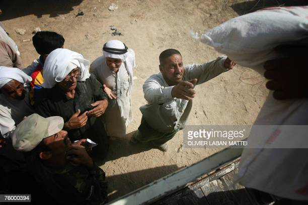 Iraqi men queue to receive humanitarian aid from the Iraqi Ministry of Trade in Baquba 60 kms north of Baghdad 05 August 2007 As Iraqis queue...