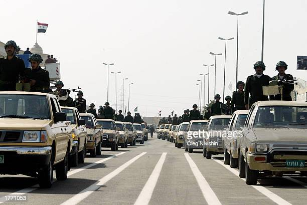 Iraqi men ride cars during a parade February 8 2003 in Tikrit Saddam Hussein's hometown Iraq Chief UN weapons inspectors landed in Baghdad for a new...