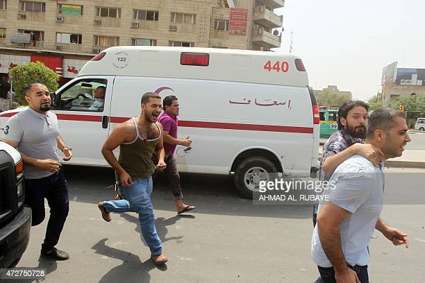 Iraqi men run past an ambulance as an injured man is taken away from the scene of a car bomb blast targeting Shiite pilgrims on an annual march to a...
