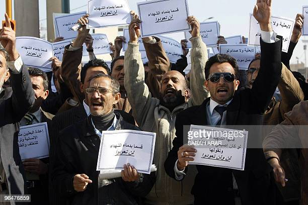 Iraqi men shout slogans and hold signs that read in Arabic We swear by the blood of martyrs you will not return during a protest in Baghdad on...