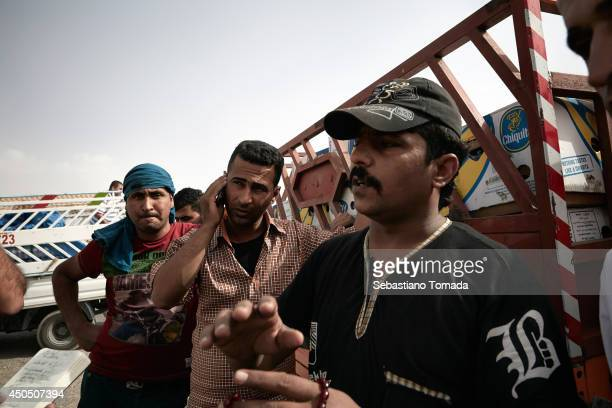 Iraqi men, some of which have defected from the army arrive at a Kurdish checkpoint in Kalak after fleeing from ISIS militants.June 12, 2014.