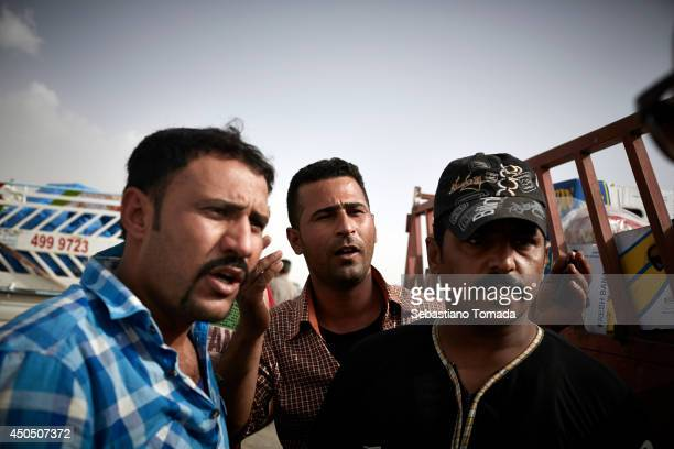 Iraqi men, some of which have defected from the army fleeing violence arrive at a Kurdish checkpoint in Kalak.. June 12, 2014.