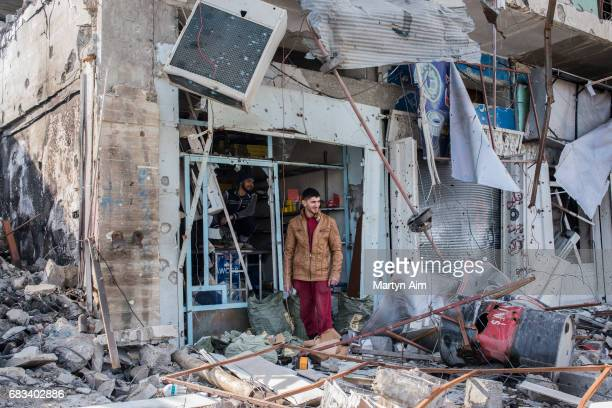Iraqi men stand in the ruins of their family business in the liberated district of Al Jazaer in eastern Mosul recently recaptured from Islamic State...