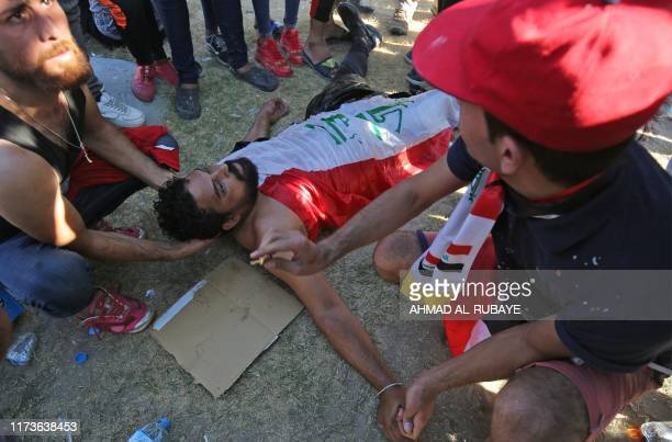 TOPSHOT Iraqi men try to help a wounded protester during a demonstration against state corruption failing public services and unemployment in the...