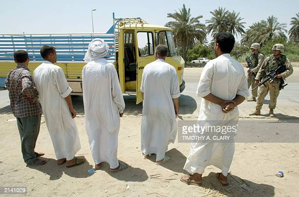 Iraqi men wait for their truck to be searched by US soldiers with the 1st Armoured Division at a roadblock near the AlMuthana Bridge in the Aazamiyah...
