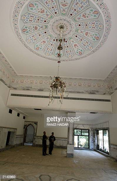 Iraqi men walk 19 June 2003 in one of the rooms in the home of toppled leader Saddam Hussein's most trusted lieutenant Abid Hamid Mahmud who known as...