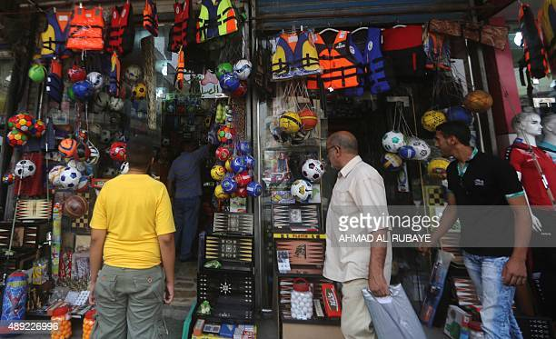 DUNLOP Iraqi men walk past a shop selling life jackets on Rashid Street where many of the Baghdad's sports shops are located on September 13 as...