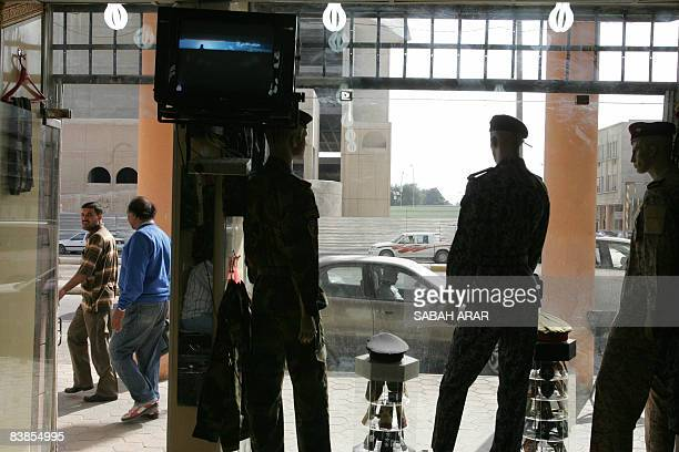 Iraqi men walk past tailor Ahmad Radi's store on Khayam Street in Baghdad on November 29 2008. Radi who has been a tailor for the past twenty five...