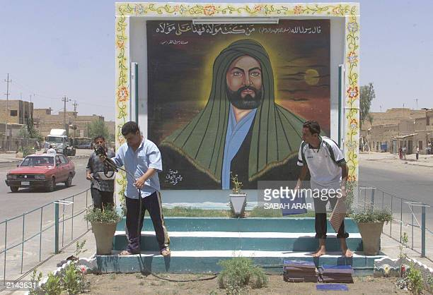 Iraqi men water the plants and lay tiles in front of a mural painting of Imam Ali the cousin and soninlaw of Islam's Prophet Mohammed in the Baghdad...