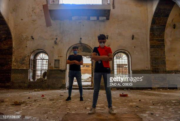 Iraqi men, wearing protective masks to combat the coronavirus , pray inside a destroyed mosque in the northern Iraqi city of Mosul on April 26, 2020.