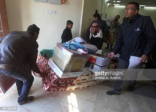 Iraqi men who fled Fallujah with their families carry mattresses and blankets distributed by the International Organization for Migration NGO on...