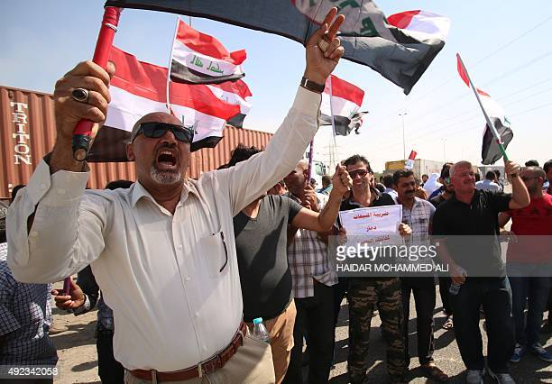 Iraqi merchants from the Basra region demonstrate outside the gate of the port of Um Qasr to scrap the new tax law on October 12 2015 Arabic slogan...