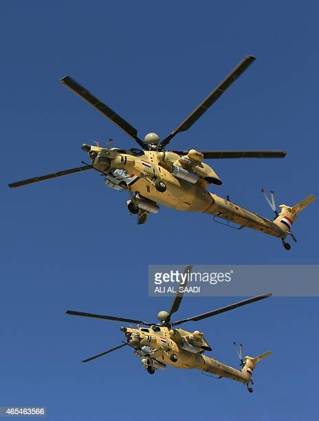 Iraqi military helicopters take part in a parade during the fourth session of the Baghdad International Fair for Defence and Security on March 7 2015...