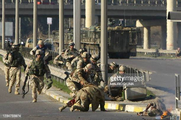 Iraqi military help their comrade lying on the ground wounded, as U.S. Soldiers from the 1st Battalion, 24th Infantry Regiment arrive at the scene to...