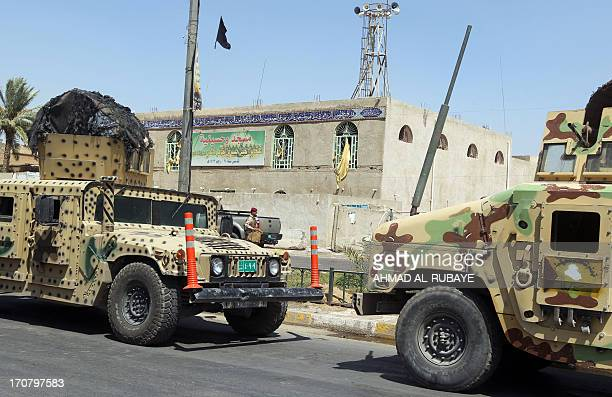 Iraqi military vehicles are stationed in front of a Shiite Muslim mosque Baghdad which was damaged following a suicide bombing on June 18 2013 Twin...