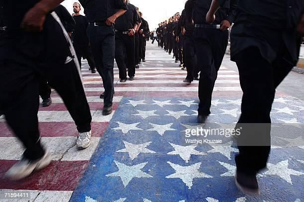 August 5 : Iraqi militiamen of al-Mahdi army, loyal to Shiite cleric Moqtada al-Sadr, walk on an American flag during a parade to mark the 2nd...
