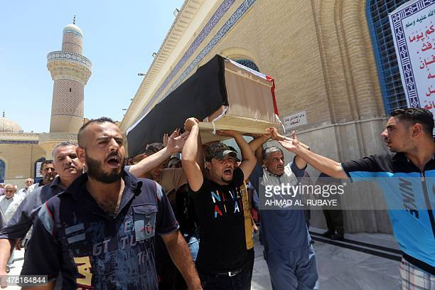 Iraqi mourners carry the casket a Sunni fighter who was a part of Iraq's Popular Mobilisation force and was killed in the town of Baiji during...