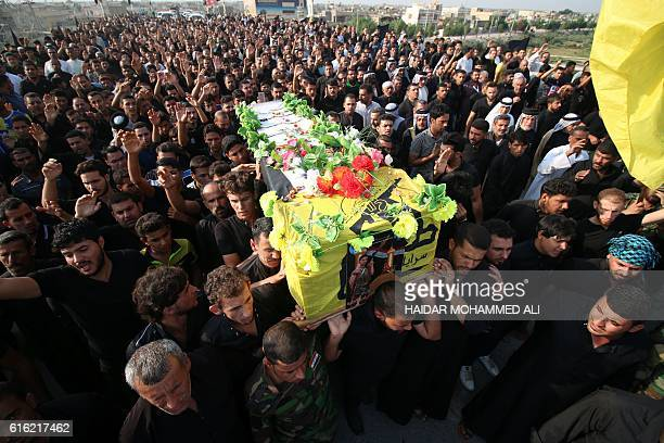 Iraqi mourners carry the coffin of Jawad alLamara an Iraqi progovernment forces' fighter who was killed in battles against Islamic State group...