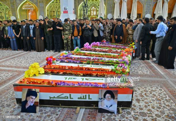 Iraqi mourners pray by coffins draped in the national flag during a funeral in the central holy shrine city of Najaf on December 13 for fighters of...