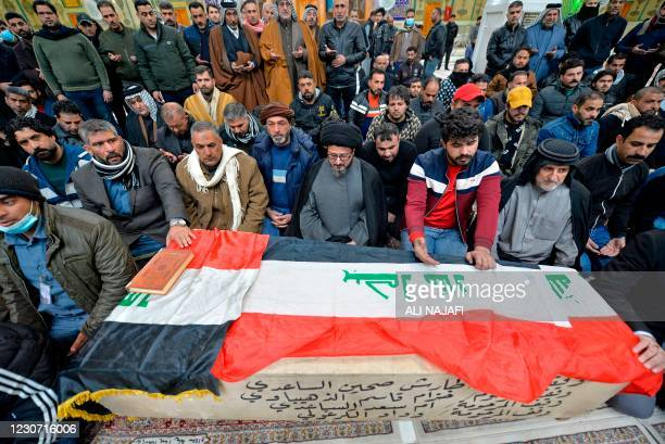 Iraqi mourners pray over the coffin of a victim who was killed in a twin suicide bombing in central Baghdad, during a funeral in the holy city of...