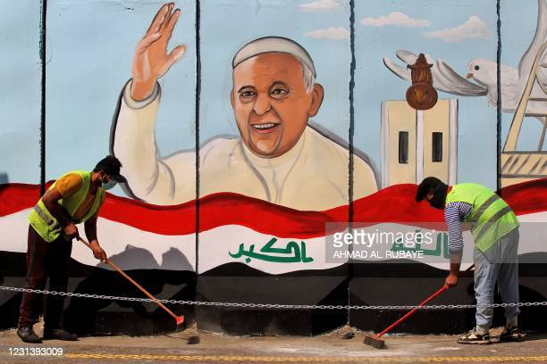 Iraqi municipal workers sweep a street in front of a giant board covered with a painting of Pope Francis and set against the wall of the Sayidat...