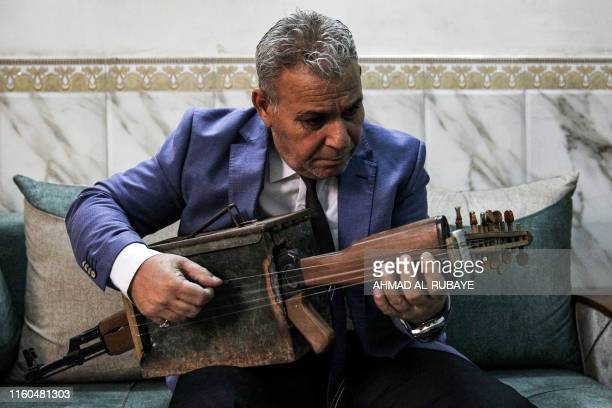 TOPSHOT Iraqi musician Majed Abdennour plays a custombuilt lute made from a Kalashnikov assault rifle and an ammunition box at his home in the...