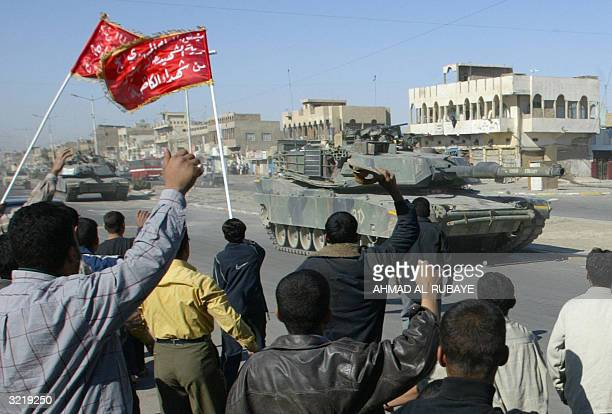 Iraqi Muslim Shiites followers of Shiite radical leader Moqtada alSadr chant antiUS slogans as two US army Abram tanks patrol a street of Baghdad's...