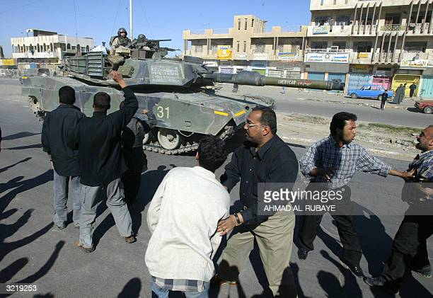 Iraqi Muslim Shiites followers of Shiite radical leader Moqtada alSadr contain their comrades as US army Abram tanks patrols a street of Baghdad's...