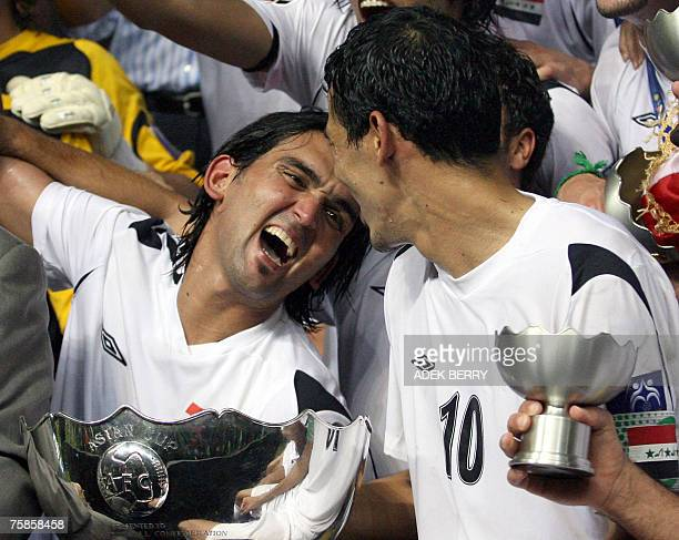 Iraqi national football player Nashat Akram shares a ligth moment to Younis Mahmoud with their winning trophy during the presentation at the end of...
