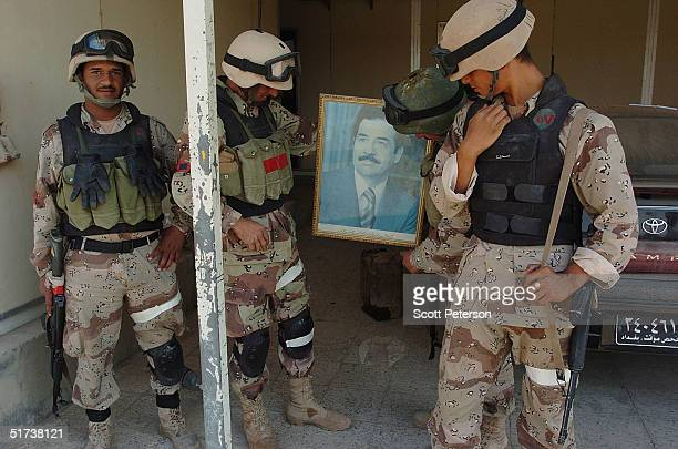 Iraqi National Guard troops show a portrait of Saddam Hussein that they found in a government office November 13 2004 in Fallujah Iraq US forces are...