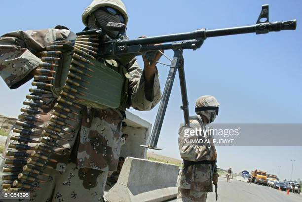 Iraqi national guardsmen stand guard at a checkpoint on the highway joining the flashpoint towns of Ramadi and Fallujah to Baghdad 13 July 2004 in...