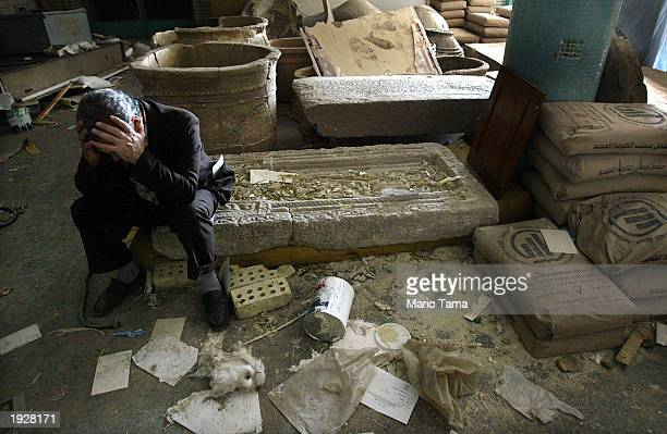 Iraqi National Museum Deputy Director Mushin Hasan holds his head in his hands as he sits on destroyed artifacts April 13 2003 in Bagdhad Iraq The...