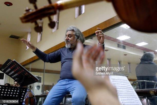 Iraqi National Symphony Orchestra conductor Mohammed Amin Ezzat leads musicians during a rehearsal on August 5 2018 at Baghdad's School of Music and...